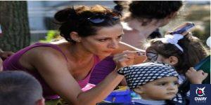 Mujer pintando a niña la cara para carnaval Cádiz