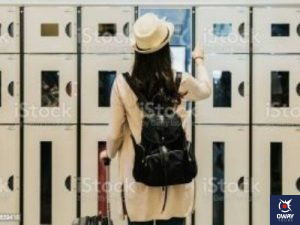 una chica con una mochila colgada está abriendo una taquilla, frente a una pared repleta de taquillas