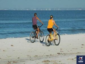 Women riding bicycles on the beach