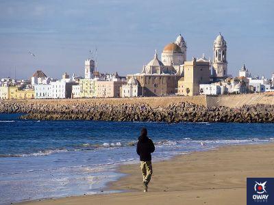Playa con la Catedral al fondo de Cádiz